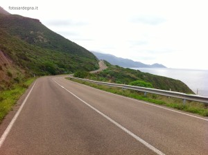 SP105 (tratto del sassarese) e in fondo il promontorio Capo Marargiu e l'isolotto Sa Pagliosa.