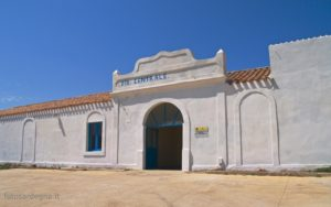 L'ingresso principale dell'ex distaccamento carcerario di Cala d'Oliva; l'edificio totalmente bianco è impreziosito dai colori celeste delle rifiniture e arancio del tetto a tegole.
