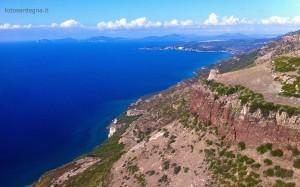 Torre Badde Jana sovrasta, dall'omonima punta, un tratto di costa smisurato, sullo sfondo le falesie di Capo Caccia.